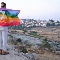 גבר חובש כיפה עטוף בדגל הגאווה