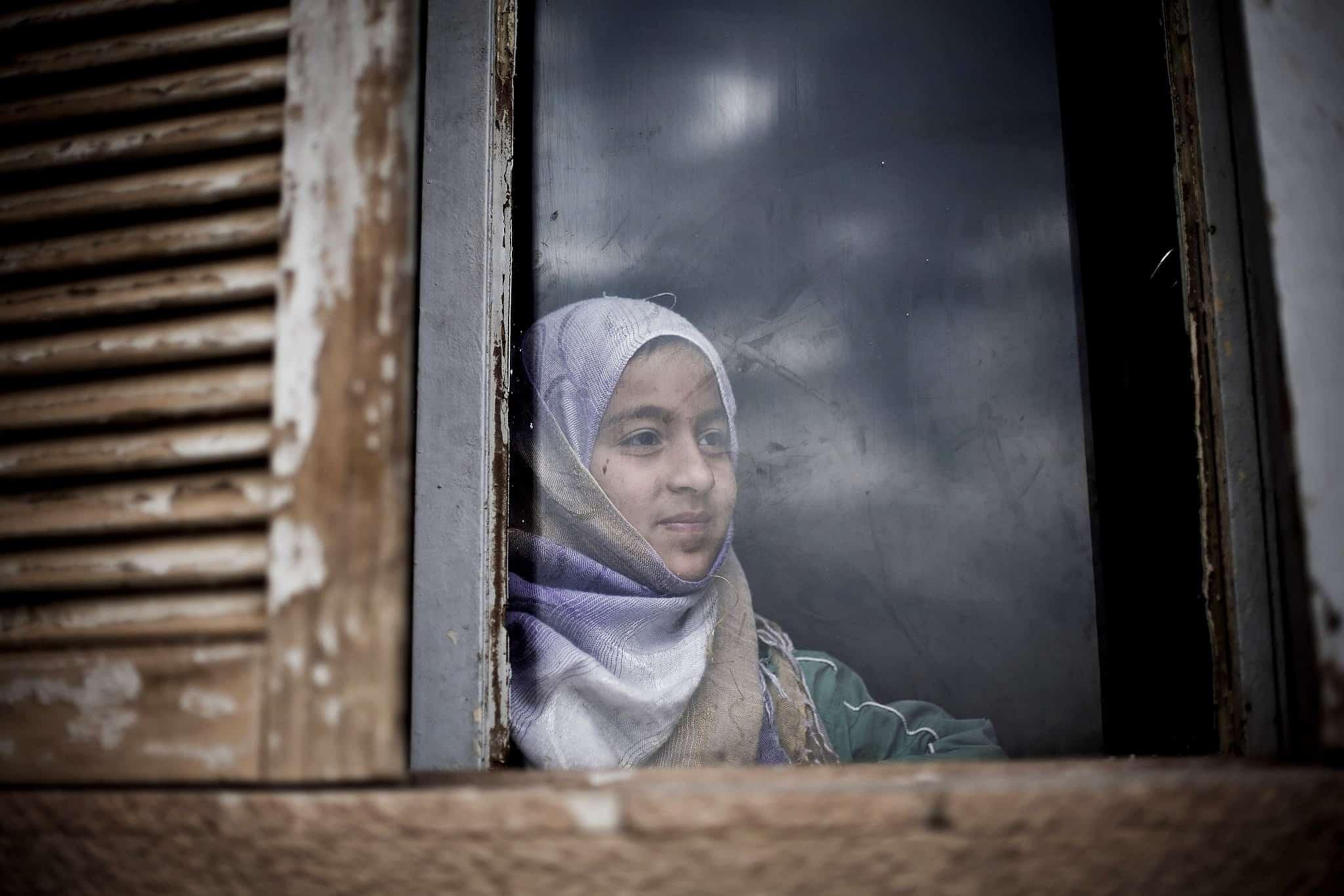 נערה סורית מביטה בחלון בית בקמישלי (צילום: AP Photo/Manu Brabo)
