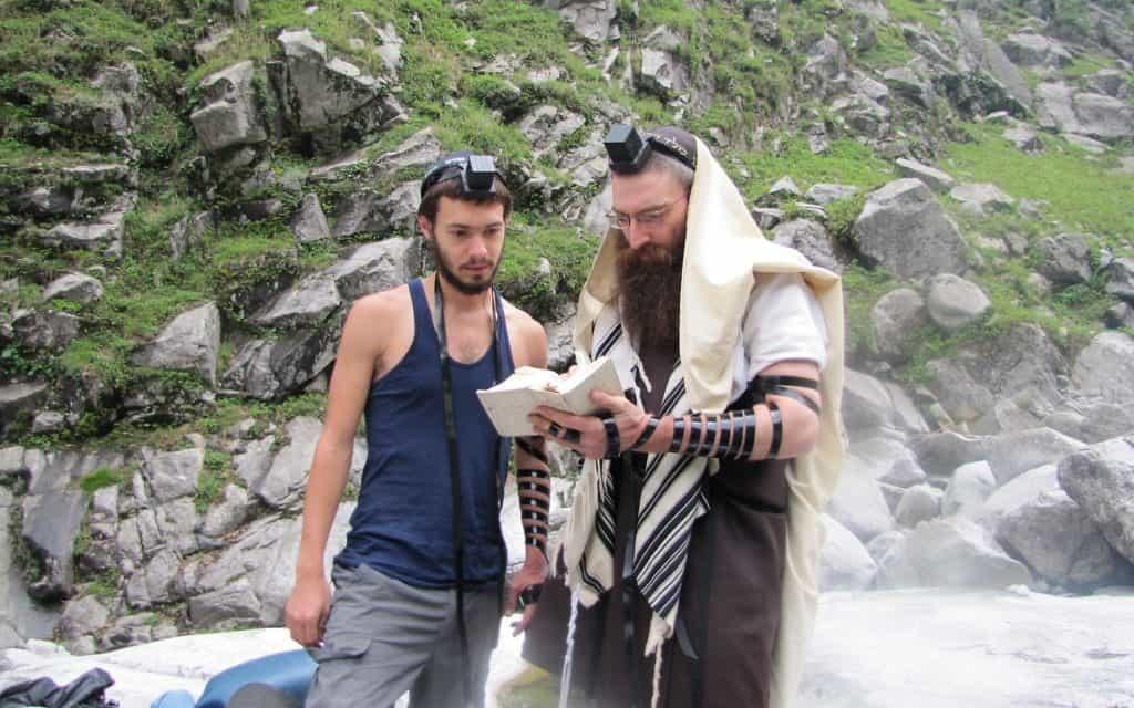 """הרב שאול עוזר לתייר להניח תפילין ליד בתי חב""""ד בהרי ההימלאיה (צילום: באדיבות Rabbi Dror Shaul)"""