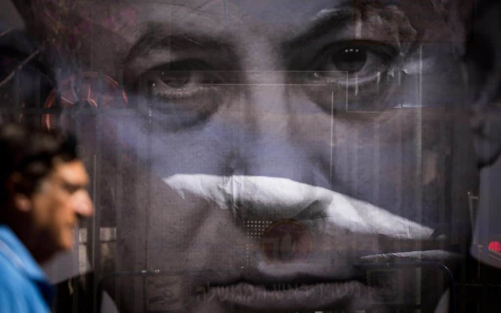 אדם עובר על יד פוסטר שמותח ביקורת על ראש הממשלה בנימין נתניהו ליד ביתו בירושלים, בזמן שחוקרים מהמשטרה באים לתשאל אותו בנוגע להאשמות השחיטות נגדו יולי, 2018 (צילום: יונתן סינדל / Flash90)