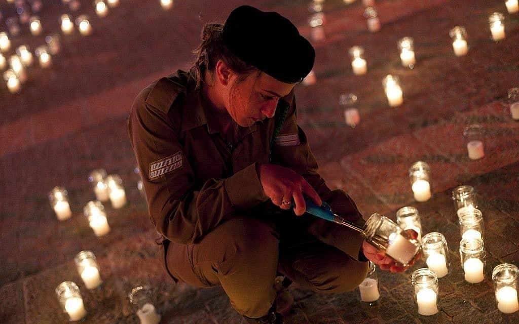 חיילת מדליקה נרות לזכר חללי צהל בטקס יום הזיכרון