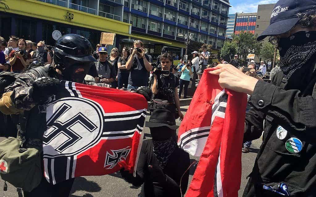 כוחות משטרה משמידים דגלים נאציים בהפגנה בפורטלנד, 2018 (צילום: AP Photo/Manuel Valdes)