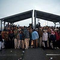 עובדים פלסטינים מוצאים מחסה מהגשם במחסום אייל, 2009 (צילום: AP Photo/Oded Balilty)