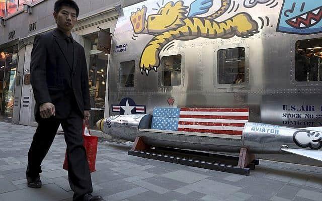 אדם עובר ליד חנות הלבשה אמריקאית בבייג'ינג (צילום: AP Photo/Ng Han Guan)