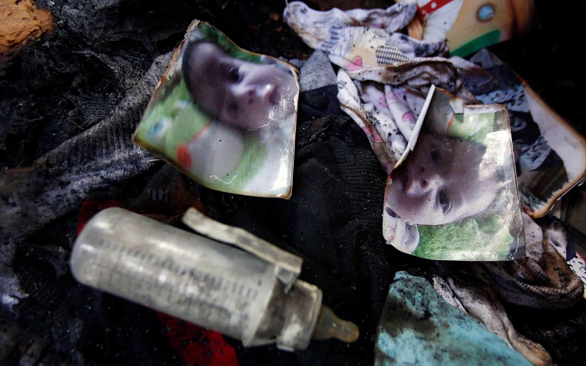 שאריות תמונתו של עלי דוואבשה מוטלות על רצפת הבית השרוף בפיגוע הטרור היהודי בכפר דומא, יולי 2015 (צילום: AP Photo/Majdi Mohammed)