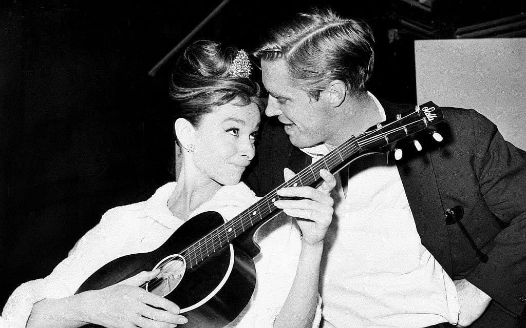 """אודרי הפבורן פורטת על גיטרה עם עמיתה ג'ורג' פפארד, על הסט של """"ארוחת בוקר בטיפאני"""" באולפן קולנוע בהוליווד, דצמבר 1960 (צילום: AP)"""