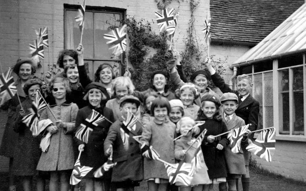 לקראת סוף תקופתה בארנהם, אודרי הפבורן (רביעית משמאל) מנופפת בדגל הממלכה המאוחדת (צילום:  אוסף דוטי)