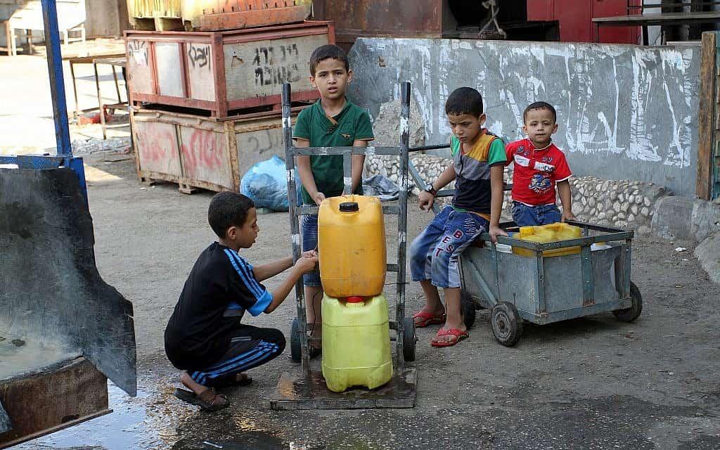 ילדים בעזה ממלאים מיכלי מים, 2015 (צילום: Abed Rahim Khatib / Flash 90)