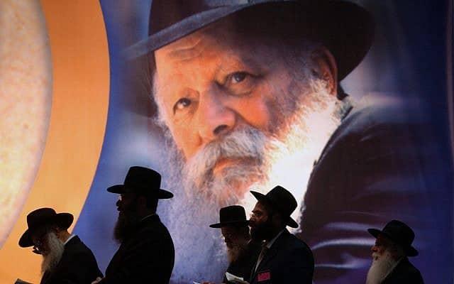 במלאת עשור למותו של הרבי מלובביץ׳, חסידים מתפללים באצטדיון יד אליהו ב-21 ביולי 2004 (צילום: AP Photo/Ariel Schalit)