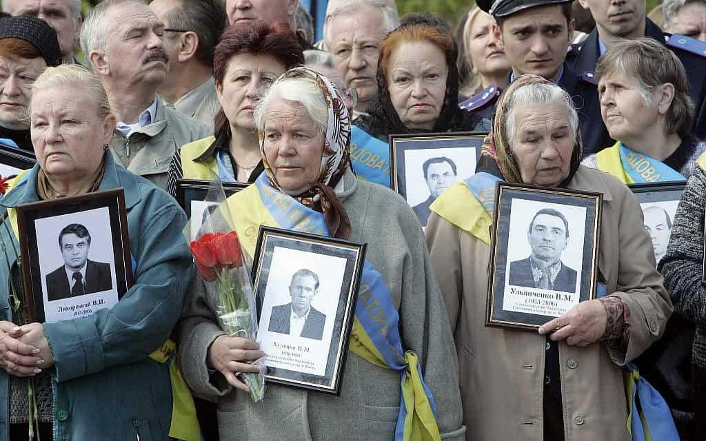 האלמנות של קורבנות צ'רנוביל עם התמונות של בעליהן שמתו לאחר פעולות הניקוי של הפיצוץ הגרעיני בצ'רנוביל ב-1986, באנדרטה לקורבנות צ'רנוביל בבירת אוקראינה, קייב, 26 באפריל, 2008 (צילום: AP\ אפרם לוקצקי)