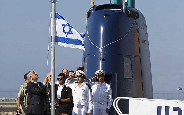 בנימין נתניהו מרים את דגל ישראל ב-23 בספטמבר 2014, בעת טקס קבלת הצוללת אח״י תנין, אחת מהצוללות שנרכשו מתיסנקרופ בגרמניה (צילום: AP Photo/Amir Cohen)