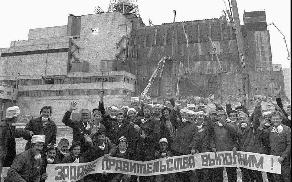 """עובדים שבנו את בסיס הבטון לסרקופג לכיסוי כור 4 המפוצץ של צ'רנוביל מצטלמים, מול בניין הכור ההרוס אשר עדיין חשוף, עם שלט האומר """"ביצענו את המשימה שקיבלנו מהממשלה"""" (צילום: AP\ וולודימיר רפיק)"""
