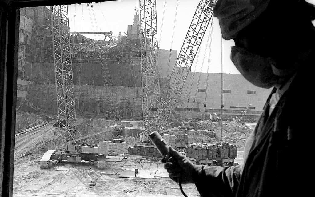 בצילום זה מ-1986, עובד תחנת הכור הגרעינית בצ'רנוביל מחזיק דוזימטר למדידת רמת הקרינה, כשברקע בניית הסרקופג מעל הכור הרביעי ההרוס (צילום: AP\ וולודימיר ריפק)