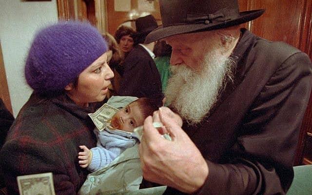 הרבי מלובביץ׳, מנחם מנדל שניאורסון, ב-1992, מייעץ לאמא צעירה לפני שתקבל ממנו דולר (צילום: AP Photo)