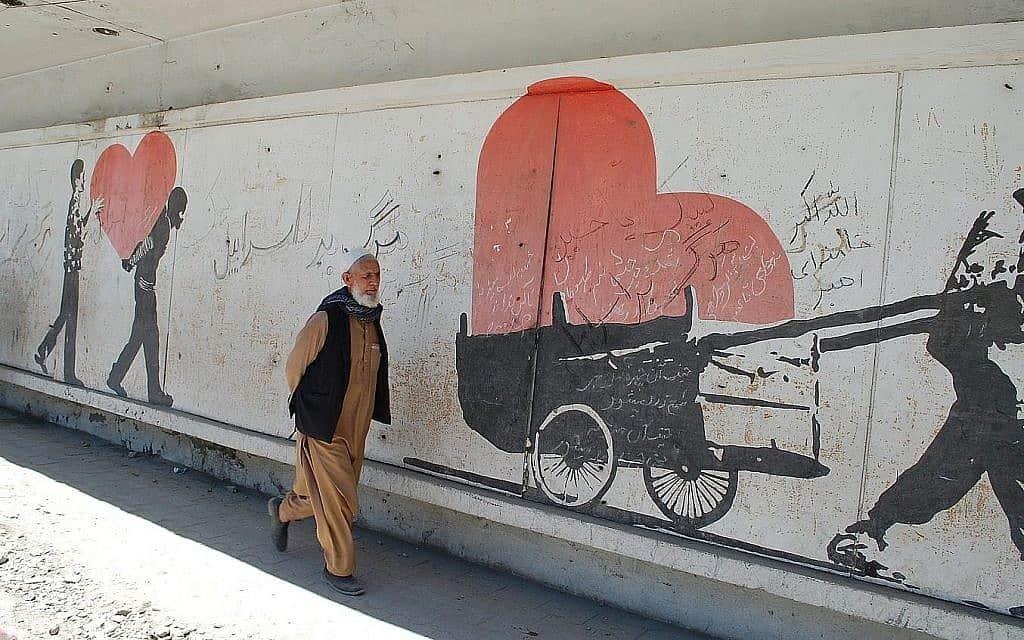 """גבר אפגני בקאבול, חולף על פני ציור קיר בסמוך לאתר של פיגוע קטלני, שכתובות עליו ססמאות """"מוות לישראל"""" (צילום: עזתוללה מהרדאד)"""
