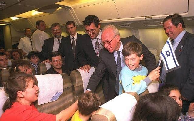 """ראש הממשלה יצחק רבין מלווה עולים מרוסיה בדרכם לארץ, 1994 (צילום: אבי אוחיון לע""""מ)"""