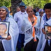 מתאבלים אוחזים בתמונותיו של סולומון טקה (צילום: Meir Vaknin/Flash90)