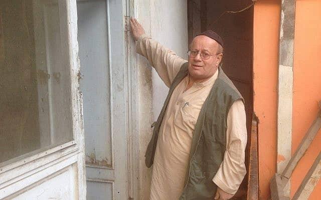 זבולון סימן-טוב נוגע במזוזה בפתח ביתו (צילום: עזתוללה מהרדאד)