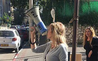 סיגל קסלר עם המגאפון, מול ביתו של נתן אשל (צילום: אמיר בן-דוד)