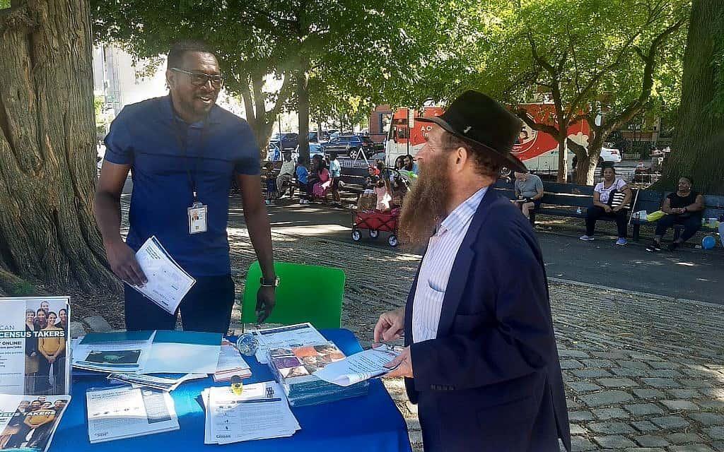 """הרב אלי כהן (מימין), מנהל המרכז הקהילתי היהודי בקראון הייטס, מדבר עם מתנדב בפסטיבל """"וואן קראון הייטס"""" (#OneCrownHeights) בברוקלין (צילום: בן סלס)"""