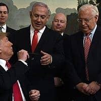 נשיא ארצות הברית דונלד טראמפ מסתובב להושיט עט לראש הממשלה בנימין נתניהו, בבית הלבן בוושינגטון, 25 במרץ 2019, לאחר החתימה על הכרה רשמית בריבונותה של ישראל על רמת הגולן. משמאל: יועצו של הנשיא ג'ארד קושנר, השליח המיוחד למזרח התיכון ג'ייסון גרינבלט, שגריר ארצות הברית בישראל דיוויד פרידמן, שגריר ישראל בארצות הברית רון דרמר ומזכיר המדינה מייק פמפאו (צילום: סוכנות הידיעות האמריקאית/סוזן וולש)
