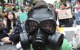 An elementary school student wears a gas mask during a rally demanding action in halting the climate crisis in Seoul, South Korea, Saturday, Sept. 21, 2019. Hundreds of activists attended a rally as a part of global climate strike ahead of a U.N. climate summit in New York (צילום: AP Photo/Ahn Young-joon)