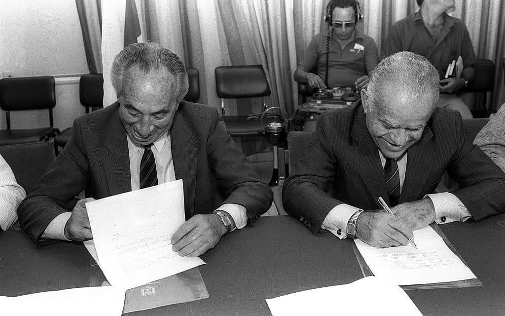 יצחק שמיר ושמעון פרס חותמים על הסכם רוטציה במשרד ראש הממשלה, ב-10 באוקטובר 1986 (צילום: חנניה הרמן/לע״מ)