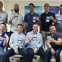 עשרה שחקני בייסבול אמריקאים מראים את תעודות הזהות החדשות שלהם לאחר שקיבלו אזרחות ישראלית, במשרדי רשות האוכלוסייה וההגירה ביפו, ב17 באוקטובר, 2018 (צילום: נבחרת ישראל בבייסבול, דרך JTA)