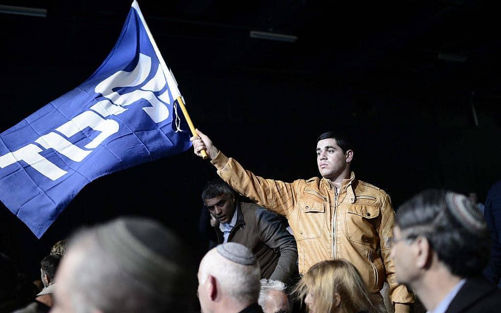 תומך מניף את דגל הליכוד בערב הבחירות (צילום: תומר נויברג/פלאש90)