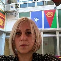 סיגל קוק אביבי על רקע דגלי מדינות תלמידי בית הספר ביאליק רוגוזין בדרום תל אביב