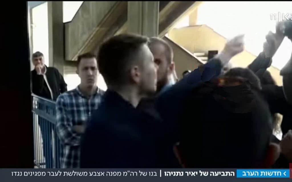 """יאיר נתניהו מרים אצבע משולשת למפגינים בבית המשפט, צילום מסך מ""""כאן"""""""