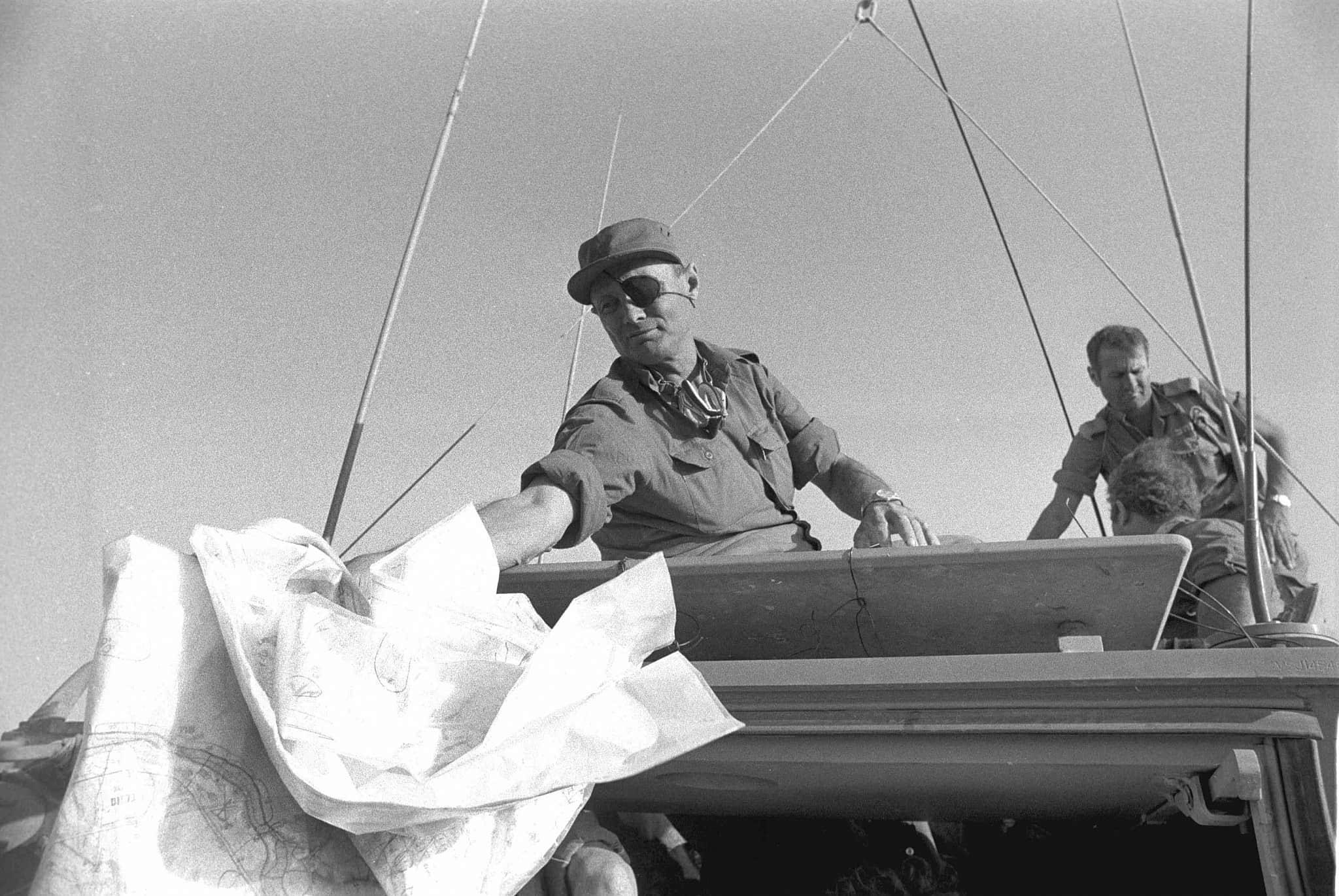 """שר הביטחון משה דיין על נגמ""""ש, מעביר מפות בביקור בצד המערבי של תעלת סואץ. 20.10.1973 (צילום: באדיבות ארכיון צה""""ל במשרד הביטחון, במחנה)"""