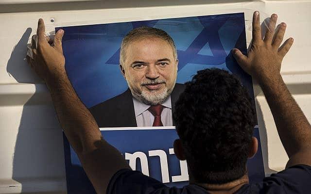 פעיל ישראל ביתנו תולה שלט עם תמונת אביגדור ליברמן לפני הבחירות בספטמבר, 2019 (צילום: AP Photo/Tsafrir Abayov)