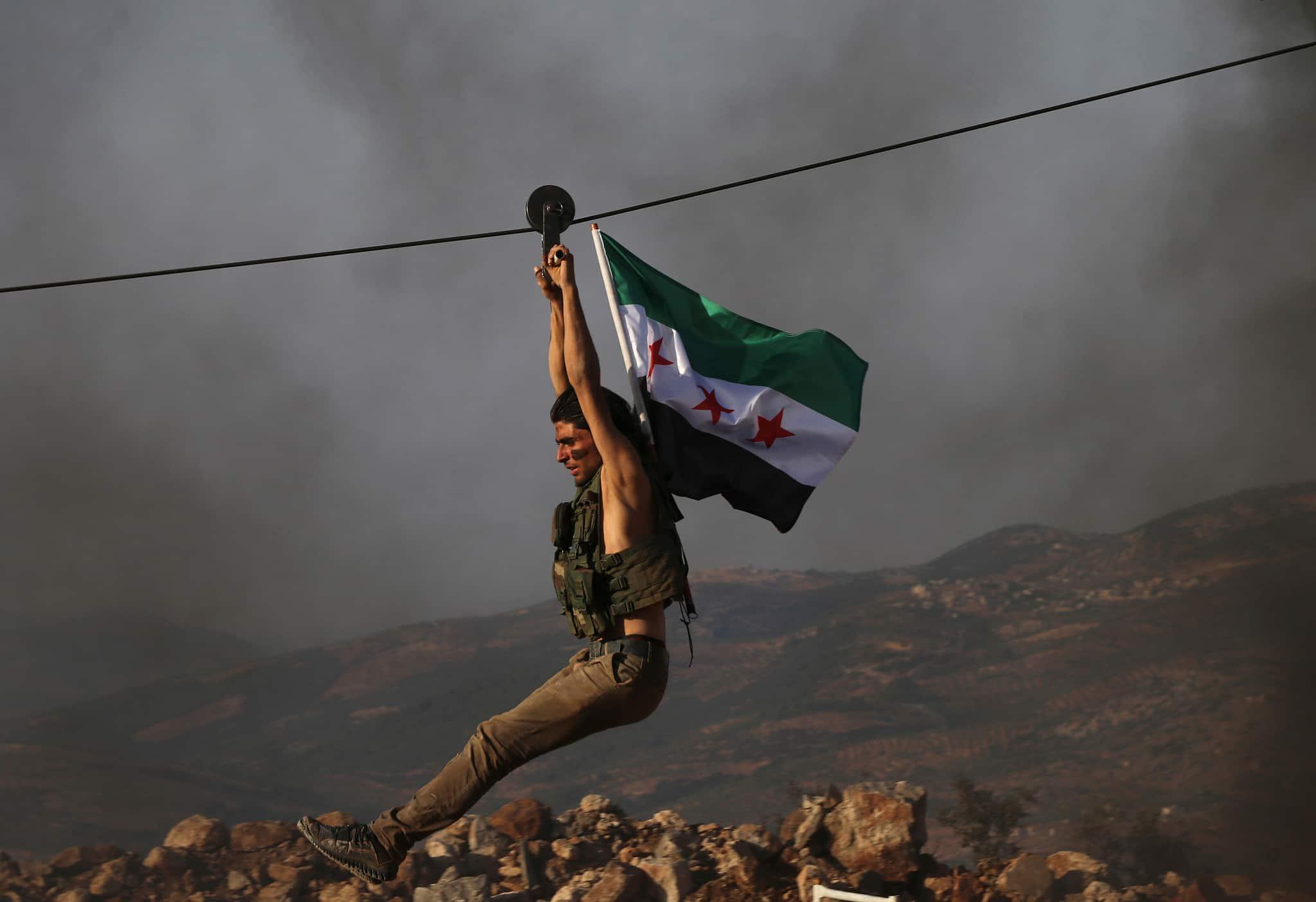 לוחם בצבא סוריה החופשית, אשר בתמיכת טורקיה, נושא את דגל הארגון במהלך אימונים בצפון סוריה לקראת הפלישה הטורקית, ב-7 באוקטובר 2019 (צילום: AP Photo)