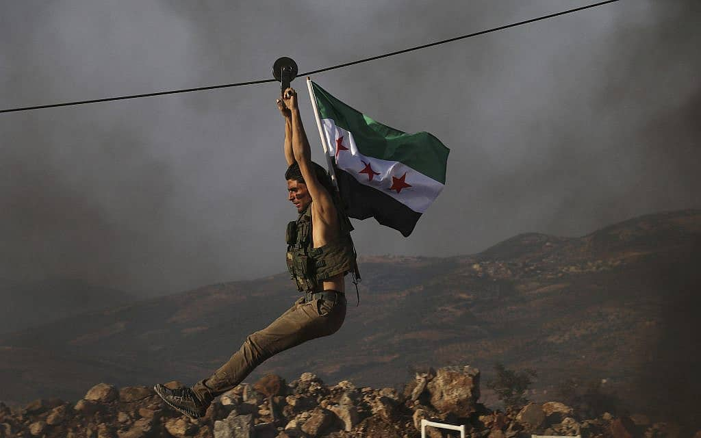 לוחם בצבא סוריה החופשית, אשר בתמיכת תורכיה, נושא את דגל הארגון במהלך אימונים בצפון סוריה לקראת הפלישה התורכית, ב-7 באוקטובר 2019 (צילום: AP Photo)