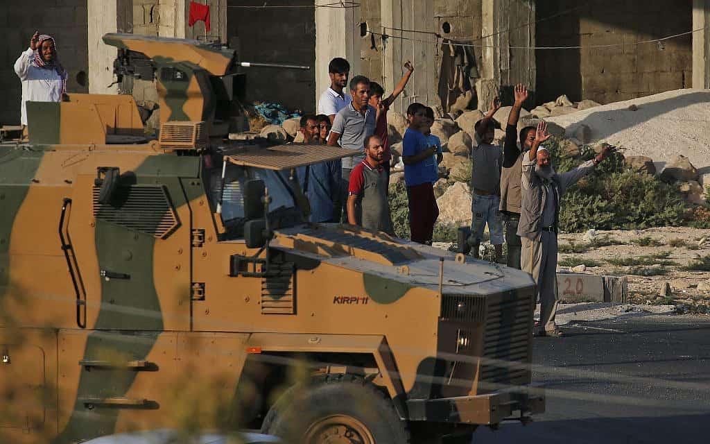 תושבים טורקים על הגבול עם סוריה מריעים לכוחות הצבא הטורקי בכניסה לסוריה, ב-9 באוקטובר 2019 (צילום: AP Photo/Lefteris Pitarakis)