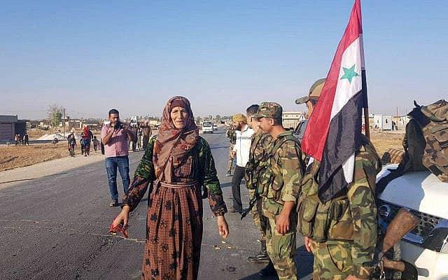 תושבים בצפון סוריה מקדמים בברכה את חיילי צבא אסד, ב-14 באוקטובר 2019 (צילום: SANA via AP)