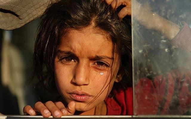 פליטה סורית מגיעה למחנה פליטים ליד מוסול, עיראק, ב-16 באוקטובר 2019. על פי האו״ם, לפחות 160 אלף תושבי סוריה נאלצו לברוח מבתיהם מאז פלישת טורקיה (צילום: AP Photo/Hussein Malla)