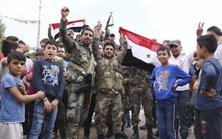 חיילים מניפים דגל סורי בכובאני, אוקטובר 2019 (צילום: SANA via AP)