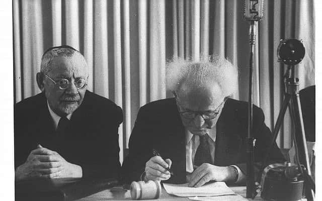 דוד בן גוריון חותם על מגילת העצמאות, משמאל הרב יהודה לייב הכהן (צילום: הנס פין, לע״מ)
