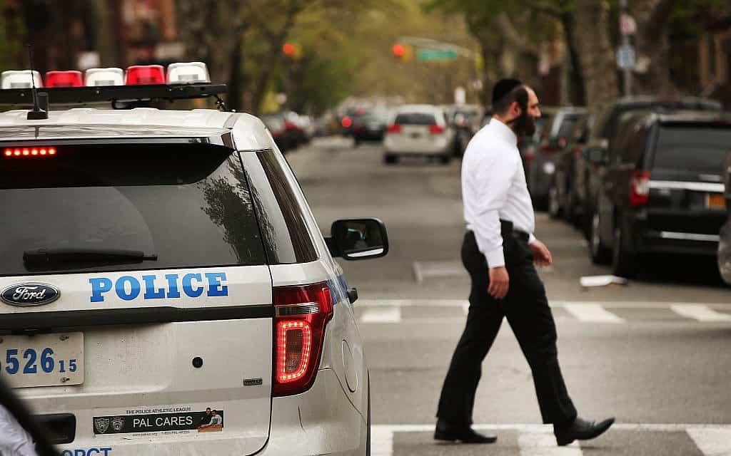 יהודי חרדי חולף על פני מכונית משטרה בשכונה יהודית חרדית בברוקלין (צילום: Spencer Platt/Getty Images)