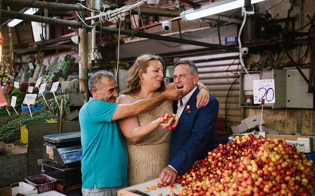 עדינה סוסמן ובעלה ג'יי שופט (מימין) טועמים דובדבנים אצל רוכל בשוק הכרמל ביום חתונתם (צילום: באדיבות עדינה סוסמן)