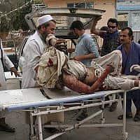 אדם מובל לבית חולים באלונקה לאחר שטיל נורה לגג מסגד במזרח אפגניסטן (צילום: AP Photo/Wali Sabawoon)