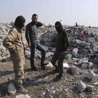 תושבים ליד מבנים שנהרסו במבצע האמריקאי לחיסול אבו בכר אל-בגדדי באידליב שבסוריה (צילום: Ghaith Alsayed, AP)