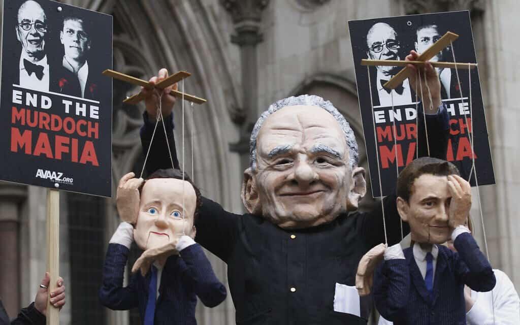 מחאה מחוץ לבית המשפט העליון בלונדון, במהלך חקירת לוויסון: מיצג של מרדוק מושך בחוטים של ראש הממשלה דיוויד קמרון ושר התרבות ג׳יימס האנט. 25 באפריל 2012 (צילום: AP Photo/Sang Tan)
