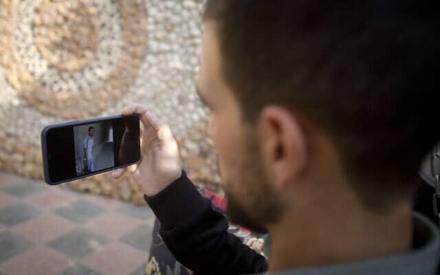 הפלסטיני כארם קוואסמי, מביט בווידיאו שצולם על ידי איש כוחו תהביטחון, המראה כיצד הוא נורה בגבו על ידי כוחות הביטחון הישראלים בתקרית בשנה שעברה, בגינת ביתו, בגדה המערבית, חברון, יום ראשון, 10 בנובמבר, 2019 (צילום: AP\ מג'די מוחמד)