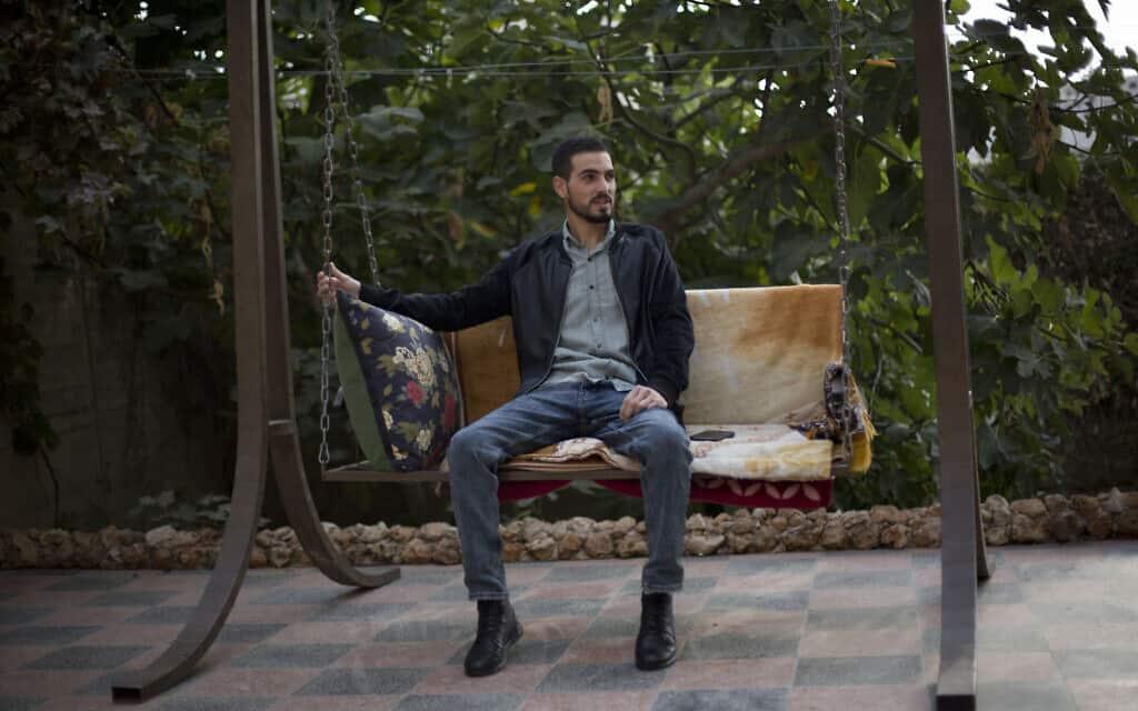 הפלסטיני כארם קוואסמי, שנורה בגבו על ידי כוחות הביטחון הישראלים בתקרית שנלכדה במצלמה בשנה שעברה, יושב בגינת ביתו, בחברון, יום ראשון, 10 בנובמבר, 2019 (צילום: AP\ מג'די מוחמד)