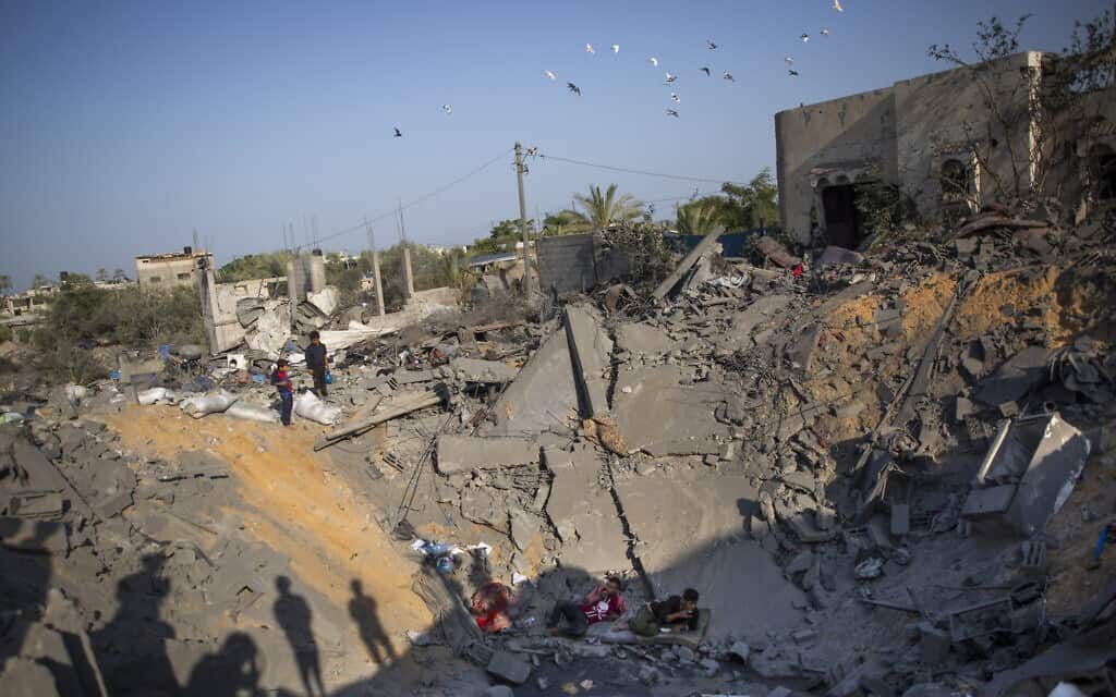 פלסטינים בהריסות ביתם בחאן יונס (צילום: Khalil Hamra, AP)