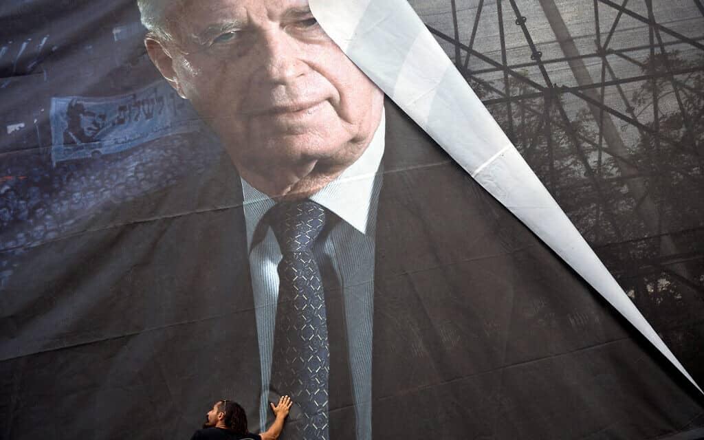 פועלים תולים כרזה לקראת עצרת הזיכרון לרגל 20 שנה לרצח יצחק רבין (צילום: AP Photo/Oded Balilty)