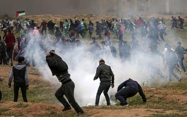 מפגינים פלסטינים מחפשים מחסה מגז מדמיע שנורה לעברם על ידי כוחות ישראלים במהלך עימותים סביב הפגנת 'צעדת השיבה', ליד גבול ישראל עזה. מארס, 2019 (צילום: מחמוד חאמס /AFP)
